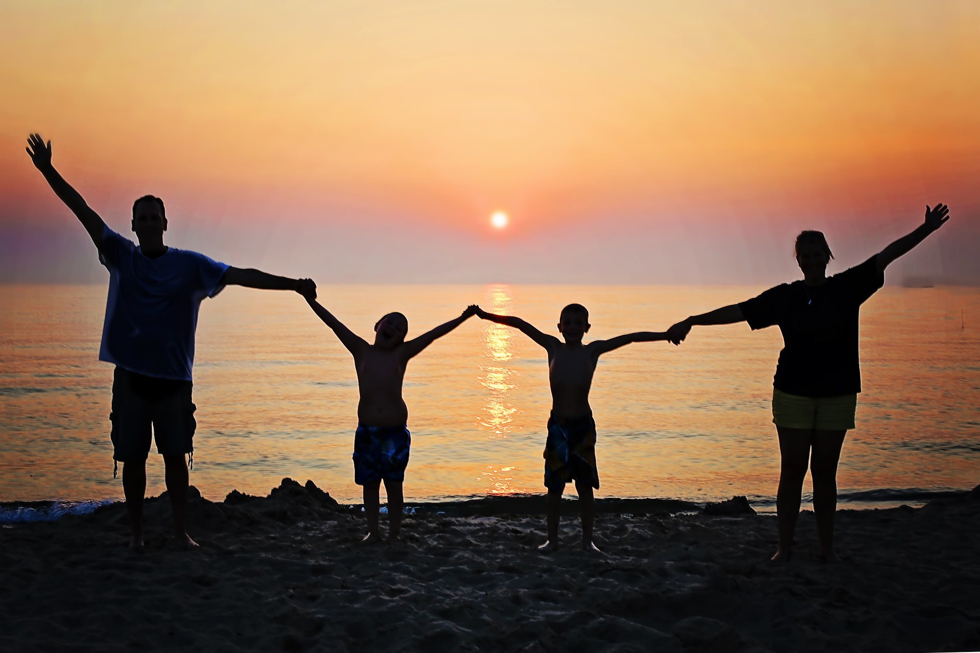 Family with arms raised, holding hands in front of ocean at sunset